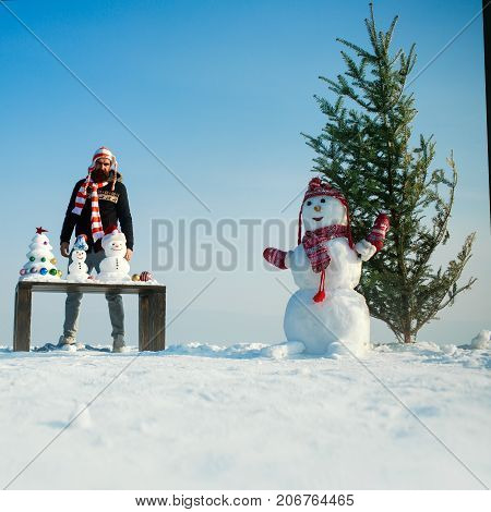 Snowman And Xmas Tree On Snowy Landscape