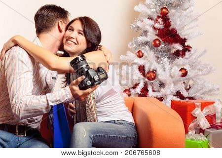 a young couple is sitting on the couch and exchanging christmas gifts. in this photo, he got a dslr camera and seems to be quite happy with it.