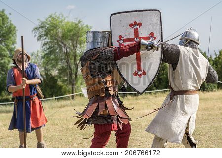 Loarre, Spain - July 09, 2016: Medieval knight battle with swords and shields, reenactment with costumed characters and medieval armor with chainmail, helmet swords and shields. Medieval demonstration and recreation