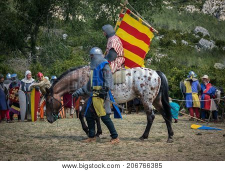 Loarre, Spain - July 09, 2017: Medieval knight riding a horse with swords and shields, reenactment with costumed characters and medieval armor with chainmail, helmet swords and shields. Medieval demonstration and recreation