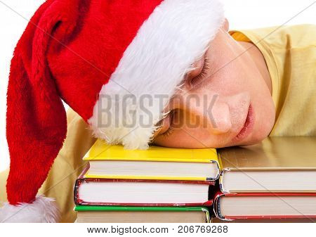 Young Man in Santa Hat sleep on the Books on a Table