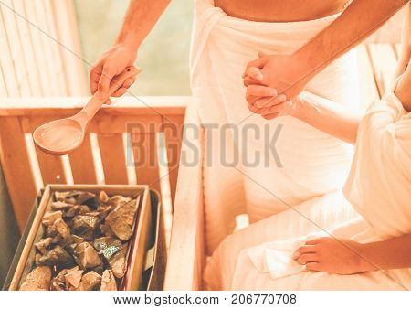 Young couple holding hands having relax in sauna at spa resort hotel - Man pouring water with spoon on hot stones - Concept of relax and bodycare - Focus on male hand poster