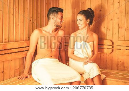 Young couple relaxing inside a sauna for cleaning and refreshing the body at spa resort hotel luxury - Romantic lovers having a bodycare day in steam bath - Concept of healthy and vacation