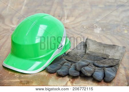 Green safety helmet and gauntlet cloves on a woode background