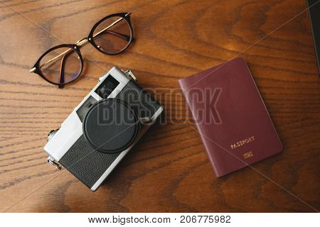 Top View. Travel Accessories Have Retro Camera, Passport And Glasses Placed On Wood Table Are Backgr