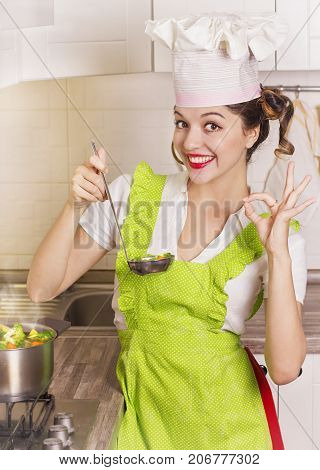 Smiling Housewife Tasting Soup With Ladle In The Kitchen