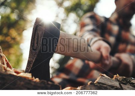Close-up Of Acute Axe In Hands Lumberjack. Blurred Woodcutter On Background