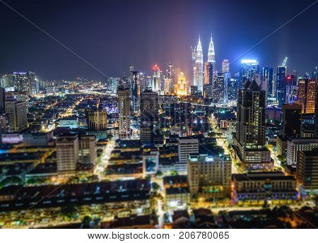 Cityscape of Kuala Lumpur city skyline at night in Malaysia. Tilt-shift effected photo.