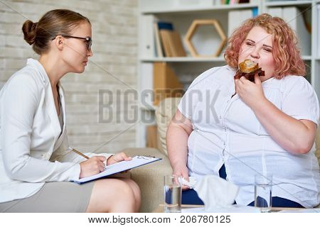 Portrait of fat young woman  eating cupcakes during therapy session with female psychiatrist