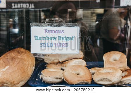 LONDON, UK - SEPTEMBER 24, 2017: Sign in a window of a famous Beigel Shop in Brick Lane that sells rainbow bagels. The shop first opened in 1855 and sells fresh bagels 24 hours a day.