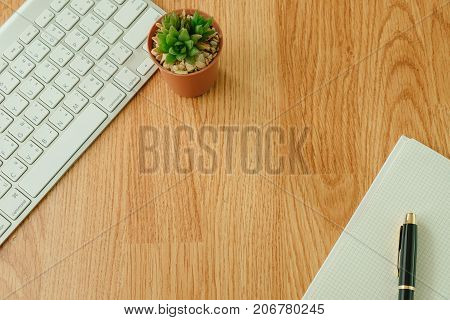 Top View. Business Equipment Include Keyboard, Plant In Vase, Pen Placed On Blank Notebook.  Wooden