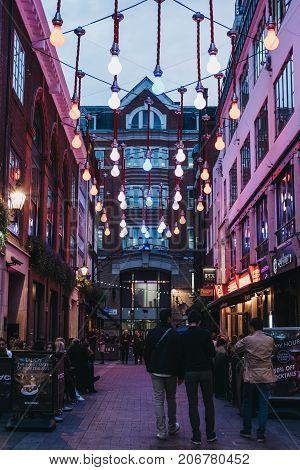 LONDON, UK - SEPTEMBER 24, 2017: People walking under lightbulb lights in Carnaby Street, pedestrianised shopping street in Soho with over 100 shops and restaurants.