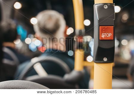 Close up of the red STOP button inside double decker bus in London, passengers on the background