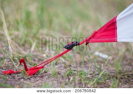 Placement of red camping tent macro shot of peg and grass