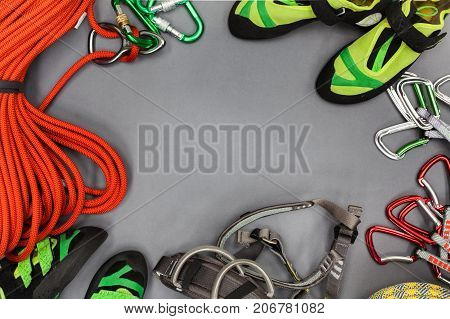 Climbing equipment laid out on on a black background. Rope climbing shoes chalk bag quickdraws belay rappel device with carabiner and other