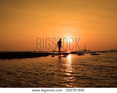 Silhouette of young man walk to the sun at sea beach with beautiful sky sunset background. To success find goal target and take action concept.