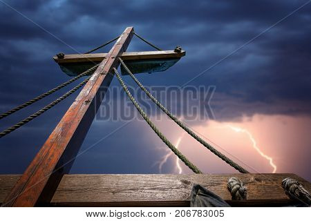 Wooden mast of a pirate ship during storm with stormy skies and lightening in the background