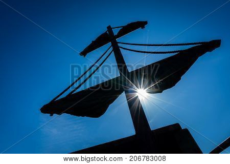 Silhouette of a mast of a pirate ship with midday sun shining over blue sky background