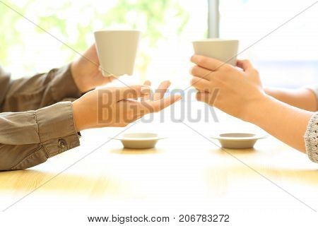 Side view close up of two women hands talking in a bar or house holding coffee cups