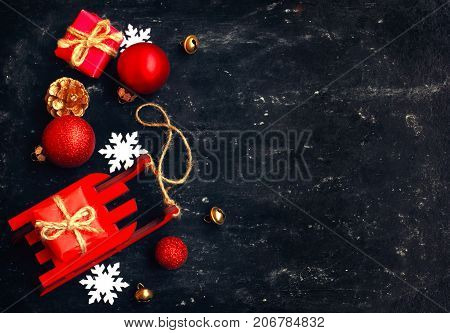 holiday christmas new year card red toy sled balls gift box snowflakes bells on black background