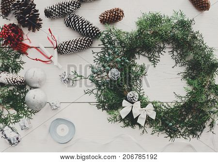 Creative diy craft hobby. Making handmade christmas wreath and fir tree garland. Tools and trinkets for holiday decorations on white wooden table with copy space.