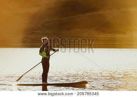 Man swims on sup paddle board at sunset time. Paddleboarding concep