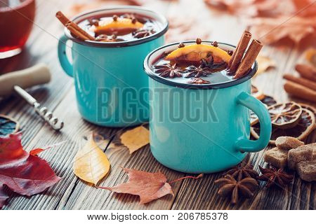 Mulled Wine In Blue Enameled Mugs With Spices And Citrus Fruit On Wooden Table With Autumn Leaves. R