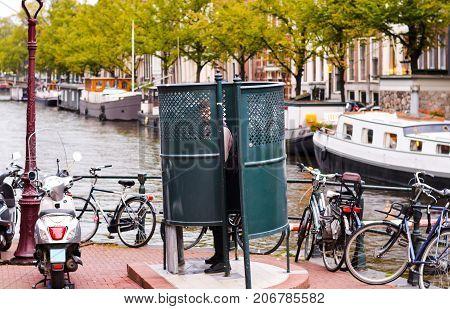 Man urinating in Amsterdam in a public urinal facility
