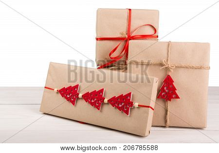 Group of gift boxes wrapped in craft paper, red satin ribbon and small toy pine trees on wooden table at white background. Modern presents for any holiday, christmas, valentine or birthday