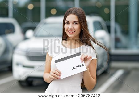 Smilling woman with agreement car service on background of dealership