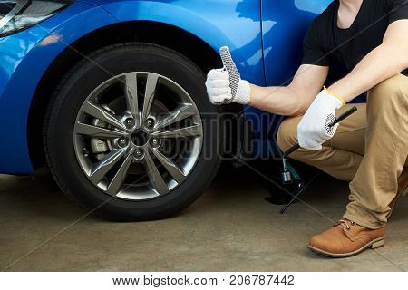 Mechanic fix car wheel. Fixed wheel on modern car