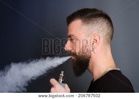 a beared man is  smoking electronic cigarette