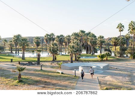 GROSS BARMEN NAMIBIA - JULY 3 2017: Unidentified tourists at the fountain of the hot springs at Gross Barmen with the swimming pool and dam in the back