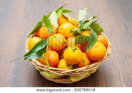 fresh mandarin oranges fruit with leaves on wooden table