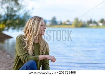 Young Thoughtful Woman Sitting By Lake
