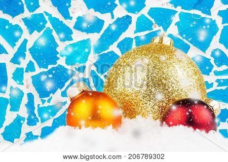 Three Christmas Balls And Blue Mosaic Background With Snow