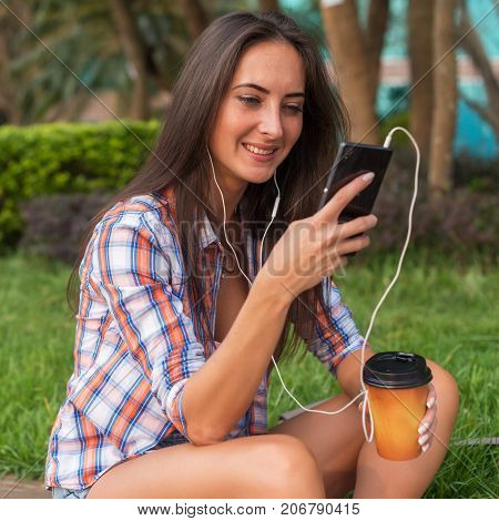Attractive young woman in headphones listening to music using a smartphone and drinking coffee while sitting on curb outdoors in the city center.