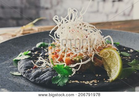 Exclusive restaurant food. Traditional hawaiian appetizer - poke with fresh salmon on black sesame flat cake on gray plate. Organic healthy meals in modern serving against white brick wall, copy space