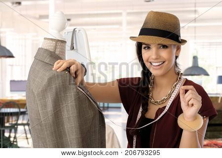 Portrait of happy young woman smiling - small business owner - woman working in fashion design business.
