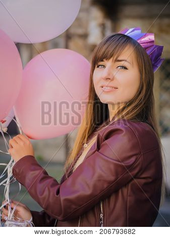 Portrait of Young happy woman with paper crown, colourful white and pink balloons smiling and laughing. Birthday girl in beautiful near old arhitecture. passage.