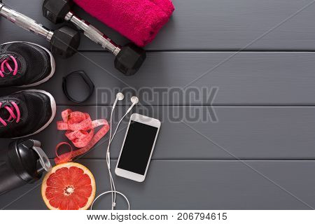 Fitness background, sport equipment, top view, copy space. Dumbbells, grapefruit, sneakers, bottle, measuring tape and blank smartphone on grey background