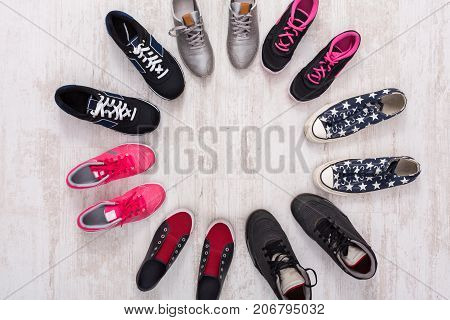 Bright and colorful sport shoes circle top view. Set of different sneakers on wooden floor, copy space. Team game, seasonal discount concept