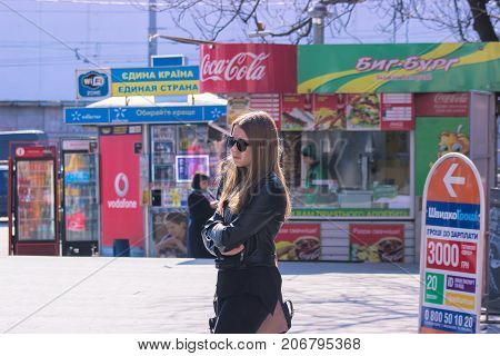 Zhytomyr Ukraine - September 05 2015: Girl wait for a bus. Bored teen waiting for parents outdoor on the metal bench sitting alone thinking and hoping expressing dissatisfied emotions