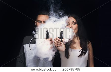 Couple vaping. Unrecognizable young man and woman in the clouds of smoke showing their vapes to camera at black studio background. Relationship and vape addiction concept with copy space