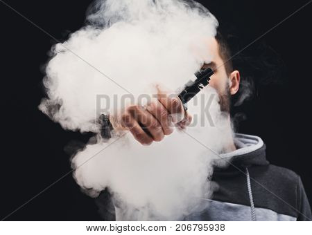 Unrecognizable man in the cloud of vape smoke. Guy smoking e-cigarette to quit tobacco. Vapor and alternative nicotine free smoking concept, copy space