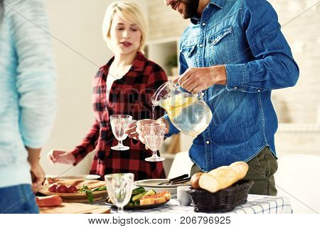 Young man pouring refreshing lemonade to glasses standing at big table with food on it while making dinner together with friends at home