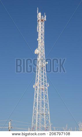 Telecom broadcasting tower network under blue sky