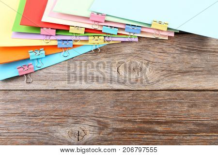 Colored Papers With Clamps On Wooden Table