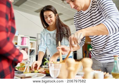 Portrait of beautiful Asian  woman preparing dinner with friends setting food on table for feasting celebration poster