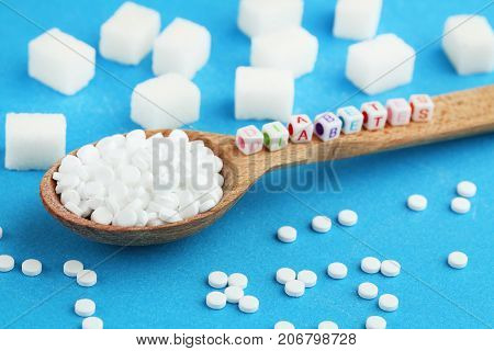 Sweetener tablets in wooden spoon with inscription Diabetes on blue background